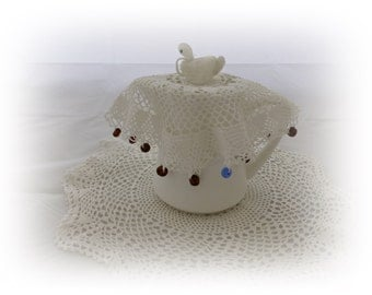 Vintage crochet jug cover with swan and blue and brown beads