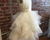 Guipure lace bodice with a high low voluminous organza ruffle skirt.