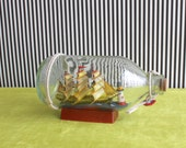 Vintage Ship in a Bottle with Lighthouse on Small Wooden Pedestal