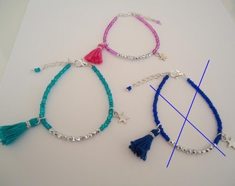 Thin beaded bracelet with a silvery star and a tassel