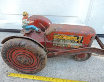 Rare red metal tractor with tin farmer