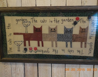 Folk art picture of cats pieced together and professionally framed.