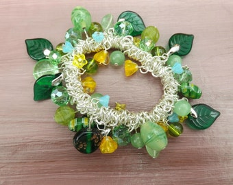 Green and yellow glass charm bracelet with tiny blue flowers on a stretch elastic base.