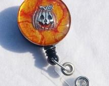 Halloween Jack-o-lantern name badge holder with an orange background