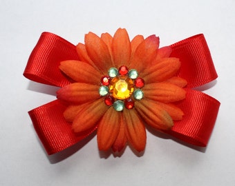 Hair Bow with red ribbon and a flower with jewels in the center on an alligator clip