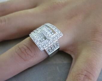 14K white gold diamond buckle ring.