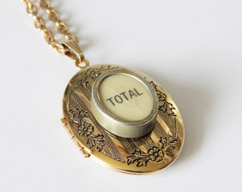 """Vintage cash register key locket necklace, """"TOTAL"""" on oval white key, shiny gold toned floral patterned large oval locket with chain"""