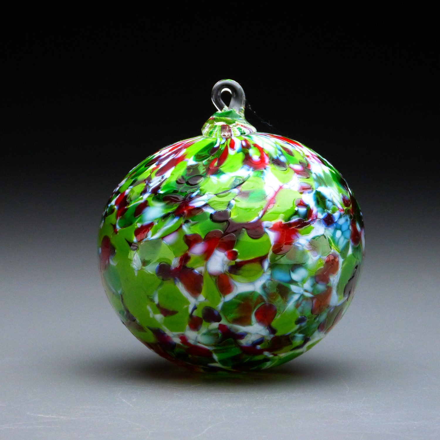 Hand made blown glass christmas ornament in tones of red