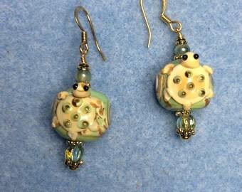 Green and tan turtle lampwork bead earrings adorned with green Czech glass beads.
