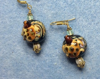 Black and brown lampwork turtle bead earrings adorned with brown Czech glass beads.