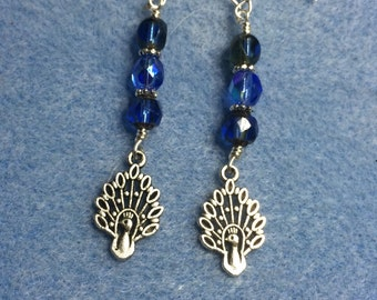 Silver peacock charm dangle earrings adorned with bright blue Czech glass beads.
