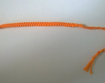 Bright orange macrame friendship bracelet.