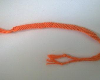 Orange friendship bracelet.