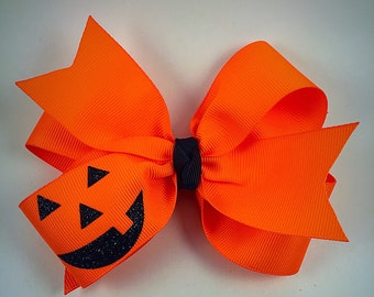 Pumpkin face hair bow / neon orange hair bow / fall hair bow / halloween hair bow