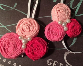 Set of 2 identical pink trio rosette elastic headband with pearls.