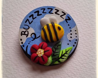 Buzzy buzzy bee in the flowers brooch made with polymer clay on a lovely round wood background.