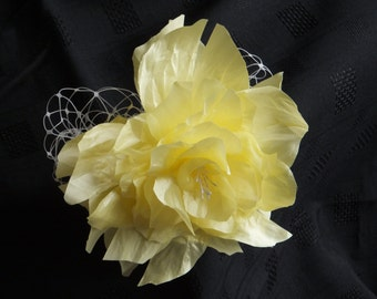 A handmade flower in yellow on a silver barrette clip trimmed with ivory veiling
