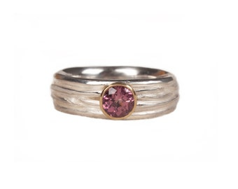 silver ring with a pink tourmaline enchased in gold