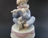 Porcelain clown playing the flute with a puppy watching him music box - Plays It's a Small World