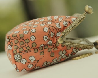Bronze metal frame coin purse/ white pearls / small grey white flowers on soft orange.