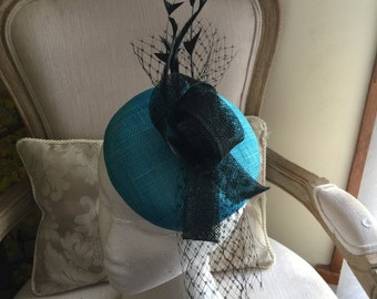 Gorgeous turqouise round fascinator with black loops, feathers and netting. Stunning!