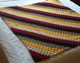 Crocheted lap afghan in blacks, reds, tans, golds and browns