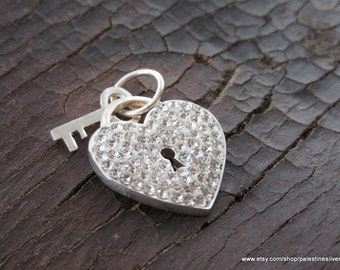 Silver pendant heart shape covered with shiny beautiful crystals with a key