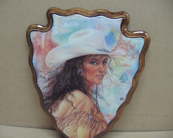 Cowgirl picture on arrowhead plaque.