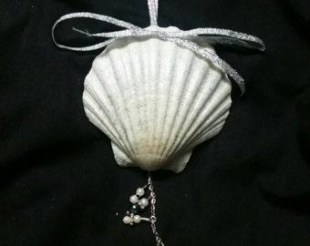 A silver glitter sea shell ornament with silver ribbon,  smoke and white pearl dangle