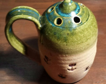 Pottery collectable,  unknown use, has holes on top, handle, open bottom. Beautiful