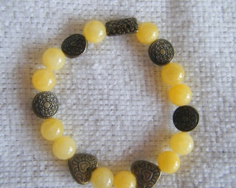 Marigold...a stretch bracelet.  Yellow glass beads with antique-bronze hearts and spacers.