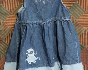 18 Mo. Little baby girl jean dress, with a little baby girl walking and picking flowers on the skirt.
