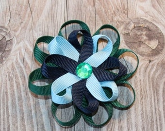 Loopy Hair Bow in green, navy blue, and light blue ribbon with a green gem center on an alligator clip