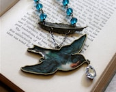 Tattoo inspired large metal bluebird and feather statement necklace with rhinestone and peacock blue glass bead accents, Birds of a Feather