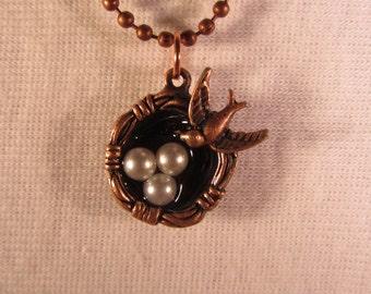Copper birds nest pendant  Birds nest with copper bird and three pearl eggs on a copper ball chain