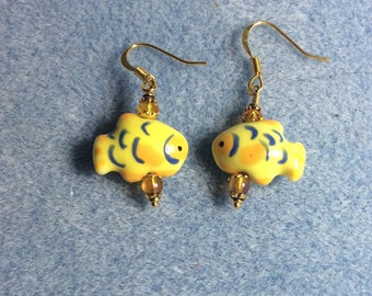 Yellow and orange ceramic fish bead dangle earrings adorned with orange glass and crystal beads.