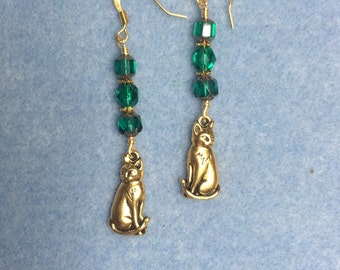 Gold cat charm dangle earrings adorned with teal Czech glass beads.