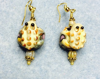 Tan and black lampwork toad bead dangle earrings adorned with tan Czech glass beads.
