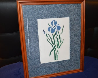 "Vintage stencil art of an Iris flower matted with blue and white vine fabric. Beautiful dark wood frame. 17.5"" x 14.5"""