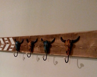 Wall coat hanger with painted skull hooks