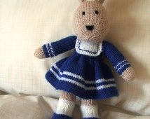 A delightful hand knitted child's toy bunny with royal blue dress  and shoes and white socks.
