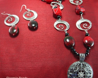 """Handcrafted 36"""" beaded necklace with pendant, shade of red, black and silver components."""