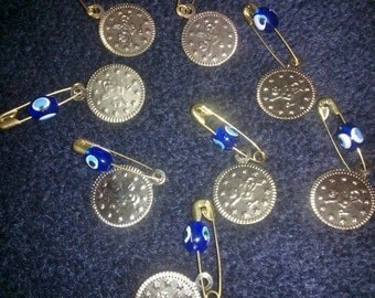 Gold plated coin and safety pin with plastic blue evil eye