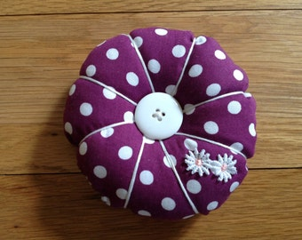Pin cushion,  bright purple spot fabric with daisy appliqué and buttons.