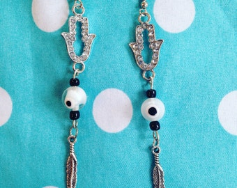 Hamsa rhinestone dangle earrings with eyeball and feather accents