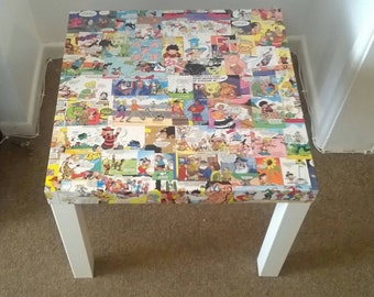 Side table with vibrant Beano decoupage finish and white legs.