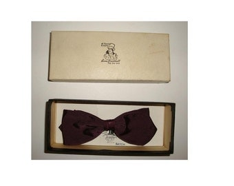 Vintage Beau Brummell Bow Tie in the original box. Snap on model made of Rayon in very good used condition. Dark burgundy in color.