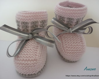 Knitted baby booties, knitted baby shoes in pink , decorated with grau ribbon.