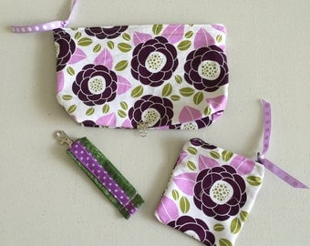 Combo deal of violet and burgundy flowers cosmetic make up case, with purple and green key fab, and a flowers coin purse.