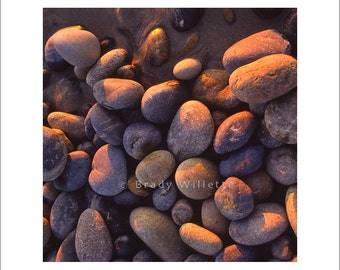 Ocean rounded beach stones with sunset light